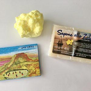 この島のお土産屋さんで見つけた硫黄石鹸(右)と、硫黄のかたまり(上)。匂いを嗅ぐと旅の記憶が蘇ります。(左)は島の特徴をよく捉えたマグネット。
