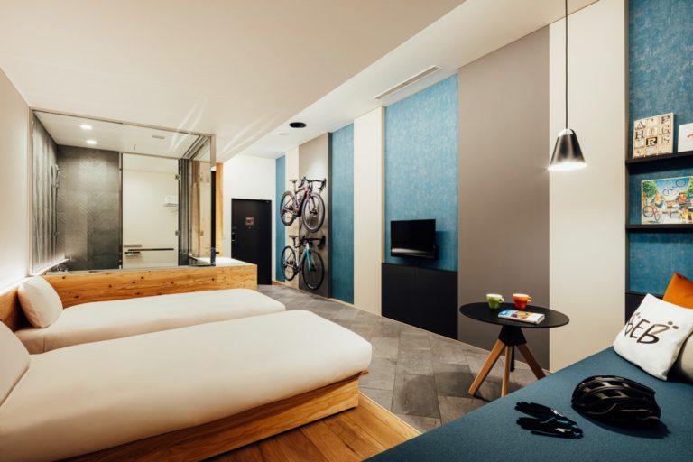 「サイクルルーム」(2名用)。1泊1室2名利用時、1名あたり6,000円~。開放的なお風呂と、ゆっくりくつろげる大きなソファーがうれしい。