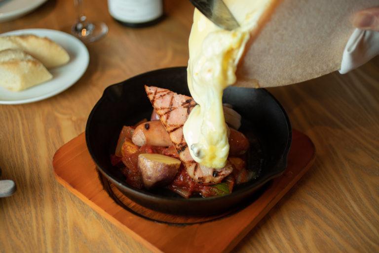 目の間で削ってくれるあふれんばかりのチーズ!「盛り合わせラクレットスキレットDish」 スイス・フランスの伝統料理。厚切り炙りベーコン、ソーセージ、蒸しチキン、ポテト、ラタトゥイユが入ったスキレットに、専用のオーブンで熱して溶けたラクレットチーズを投入。2,420円。チーズ好きは、追加ラクレットチーズ1,078円も!