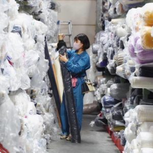 〈株式会社ヤギ〉の生地が保管されている倉庫にて。膨大な量のサンプル生地の中から、〈coxco〉のコンセプトやデザインに合うものを探す。