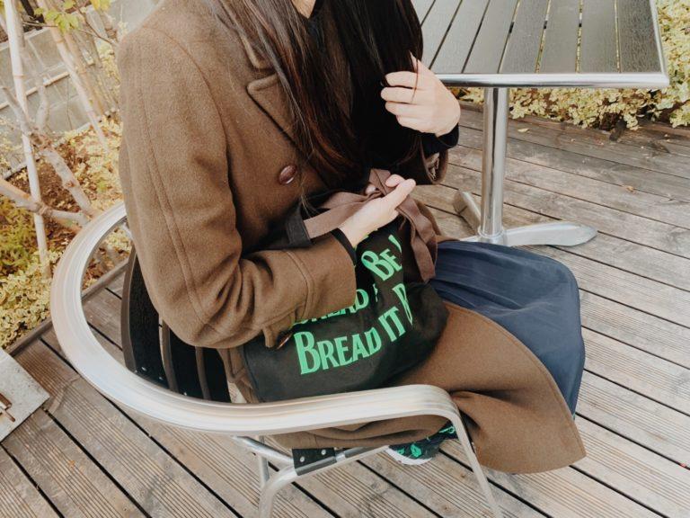 ちゃっかり〈BREAD IT BE〉バッグを右手に。