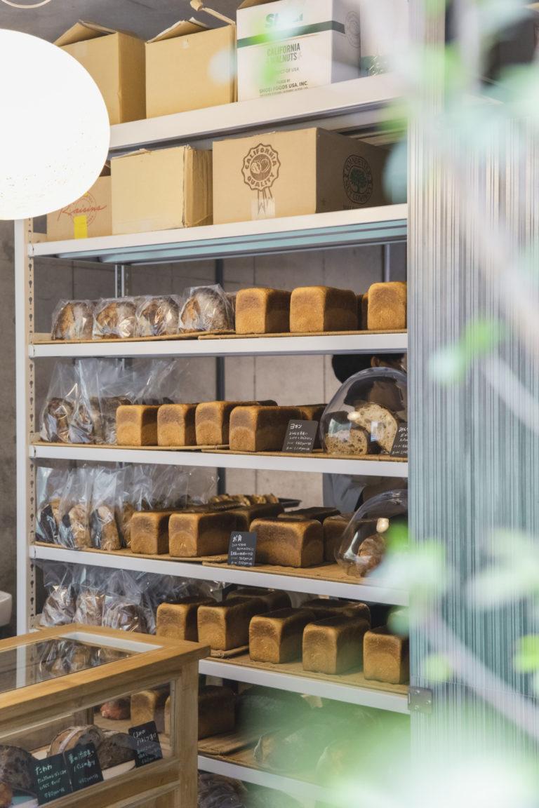 角食パン「お角」360円が並んだ棚。左・中村隆志シェフ。4種類の発酵種を巧みに操り、長時間熟成を経てありえない風味・食感のパンを生みだす。