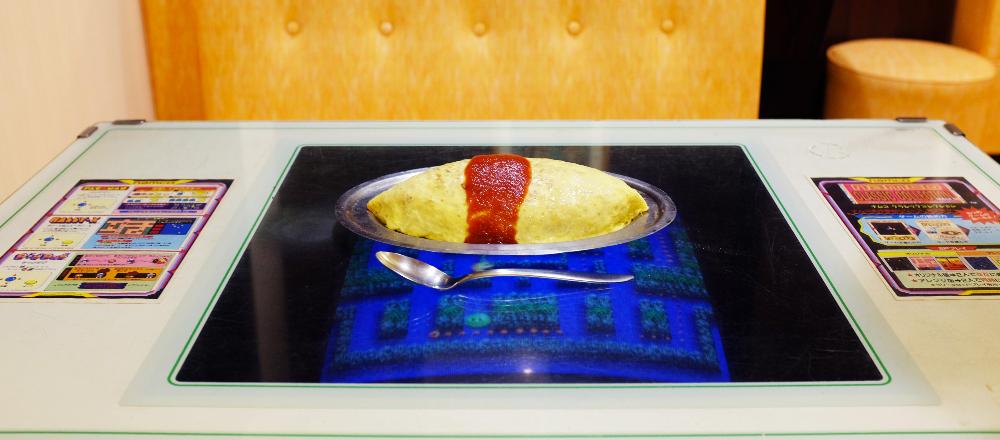 昭和レトロすぎる浅草の喫茶店〈デンキヤホール〉。ゲーム台の上でオムソバを頬張る。/Alice in Cafeland
