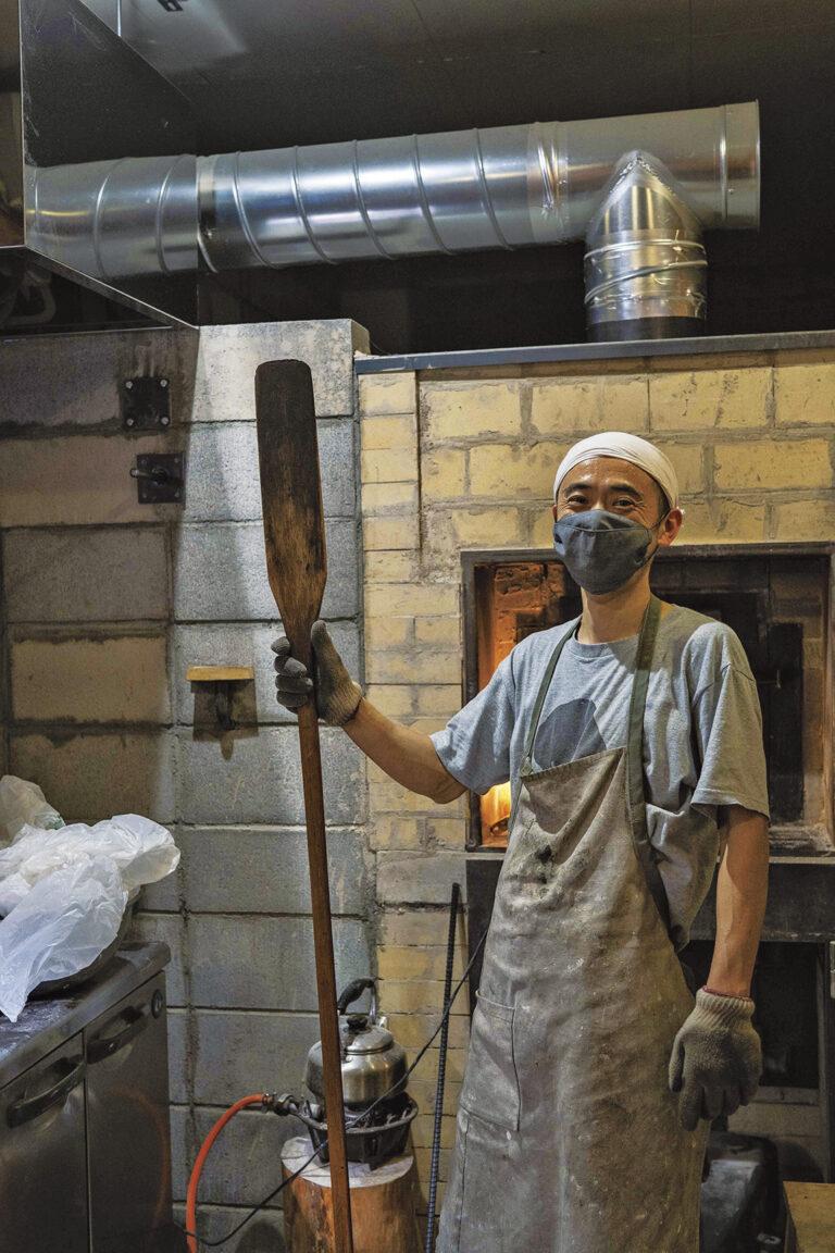店主の塩見聡史さん。修業先である沖縄の薪窯パン屋〈宗像堂〉で卒業記念にもらったピールを手に。