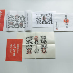 三本足でサッカー日本代表のシンボルでもある八咫烏は熊野三山の神を総称した熊野権現の神使。そのため護符は独特のカラス文字で書かれている。右上から時計回りに、熊野本宮大社の熊野牛王神符、熊野那智大社の烏牛王神符、熊野速玉大社の熊野牛王宝印。
