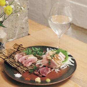 宮崎県産 黒岩土鶏のたたき盛り合わせ1,500円。新鮮さがものを言う九州の名物だ。焼酎の水割り580円~はワイングラスで香りも楽しむ。