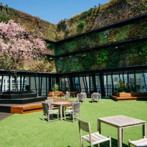 鮮やかなグリーンウォールや春には桜が目を喜ばせる〈グリーンサイド〉は、広々とした空間にテーブルやチェアが配された開放的なスペースです。