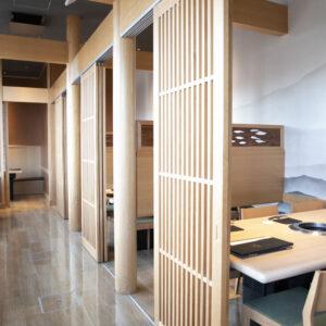 木を基調とした洗練された雰囲気の店内。眺望のいいガラス張りのカウンター席やテーブル席、個室など豊富に用意。