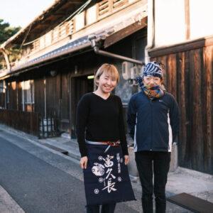 今田酒造本店にて、美穂さんと。いただいた前掛けをつけて。