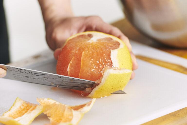 グレープフルーツの頭とお尻をカット。残った皮は包丁でなぞるように切るとむきやすい。