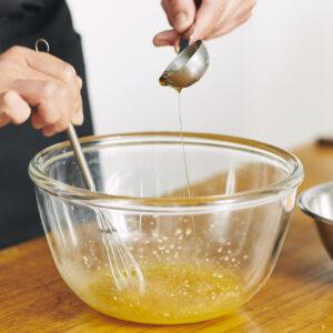 ボウルでドレッシングを混ぜながら、少しずつオリーブオイルを加えることで分離を防止。
