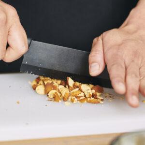 包丁のサイドをアーモンドに当て、体重をかけながら砕いていく。