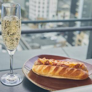 ルーフトップバーで名物のホットドッグに舌鼓。〈メゾンカイザー〉のパンにこだわりのソーセージを挟んだ名物のホットドッグは、「チリ」1,200円をはじめ、「アメリカ」や「イタリア」など6種類。スパークリングワイン(グラス)1,000円(各税込)などアルコールも充実。