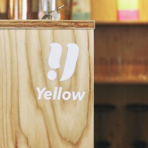 カジュアルな木製カウンターにYellowのロゴ。