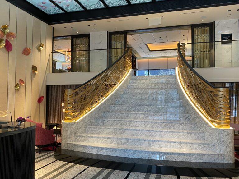 1階エントランスで出迎える、きらびやかなゴールドと大理石の大階段。天井のステンドグラスや壁の装飾には、咲き誇る桜が一面に。