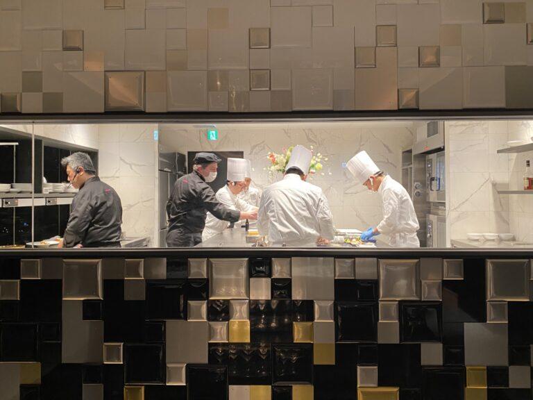 真っ白な大理石張りのキッチンはシェフのステージのよう。左は枡直人エグゼクティブシェフ、この日は〈フォション ジャパン〉総料理長、セドリック・マトン氏の姿も(中央)。