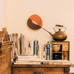 お茶箱の上にセルフサービスのお水。隣の古い机には喫茶店の雑誌や本が置いてあり、レトロな雰囲気。