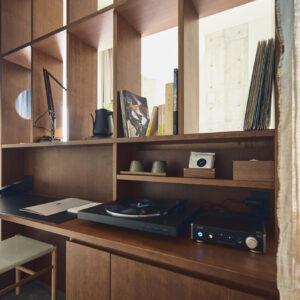 レコードの持ち込みもアリ。ベッドのヘッドボードの裏は、なんとデスク!ワーケーションにも最適。藍染のカーテンは、東京下町の〈内田染工場〉によるもの。