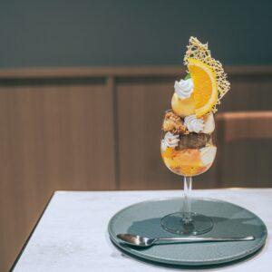 橙色が鮮やかなパフェ。グラスの中の余白がため息をつくほど美しい・・・。