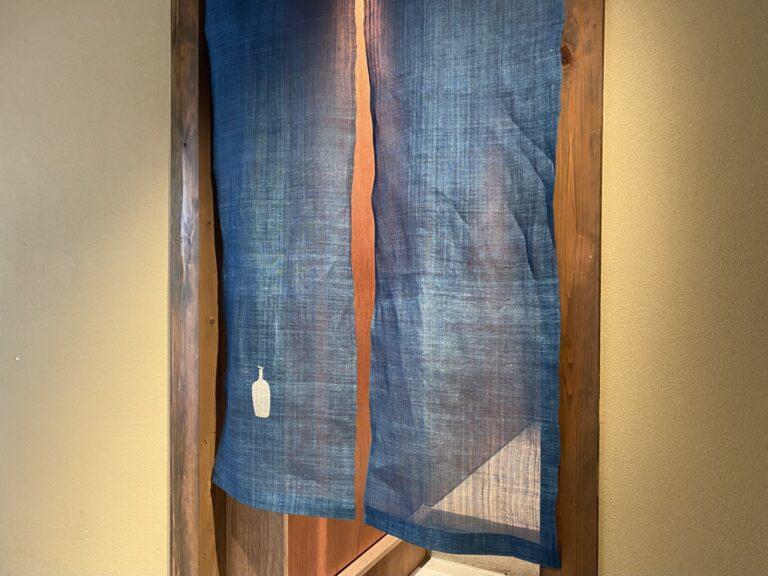 京町家と調和する藍染の暖簾。靴を脱いでラウンジへどうぞ。