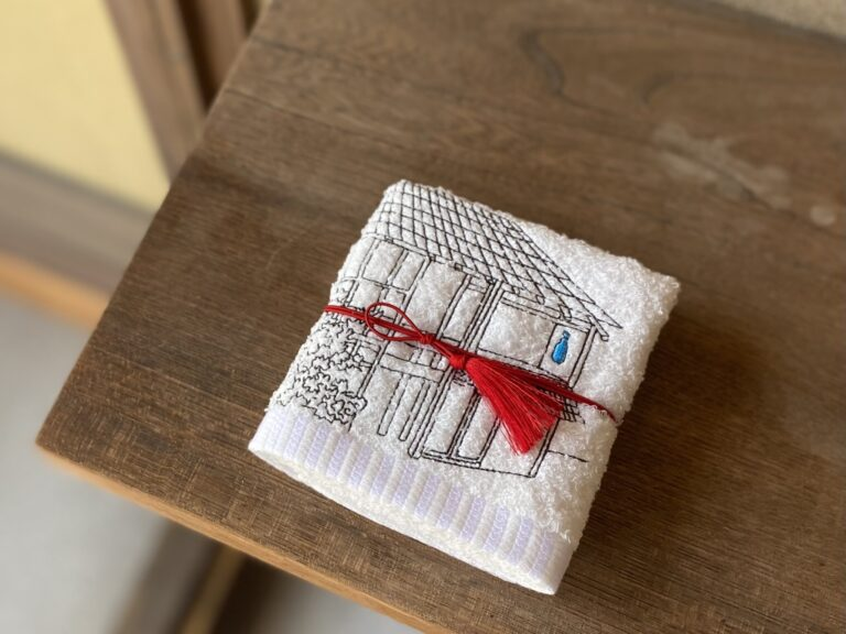 リニューアル記念アイテムも登場。京都の刺繍ブランド〈京東都〉とのコラボで誕生した、京都カフェの外観を刺繍した愛らしいハンドタオル。大阪の〈泉州タオル〉を使用。1700円。*〈京都カフェ〉限定販売。