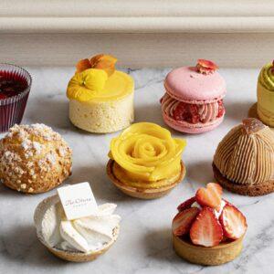 左奥から「ハイビスカスとベリーのジュレ」、「レアチーズケーキ」、「ラズベリーとライチのマカロン」、「ピスタオムース」、「シュークリーム」、「マンゴークラフティー」、「モンブラン」、「レモンパイ」、「苺タルトレット」。