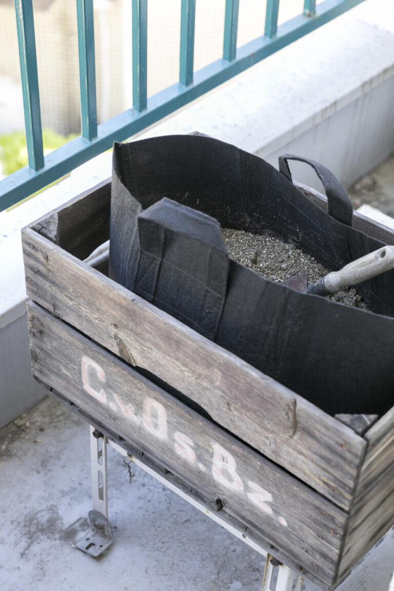 E.生ゴミを肥料に変えて生かすベランダコンポスト。土に生ゴミを混ぜ、微生物の働きで堆肥に変えるコンポスト。木箱にホームセンターで買ったコンポスト用バッグをセットして、マンションのベランダで実践中。「現在2年目。ゴミが減る心地よさがやみつきに」