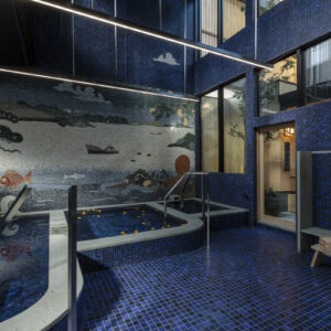 宿の向かいに立つ銭湯とサウナ、湯上がりラウンジ、客室を備えた〈yubune〉。