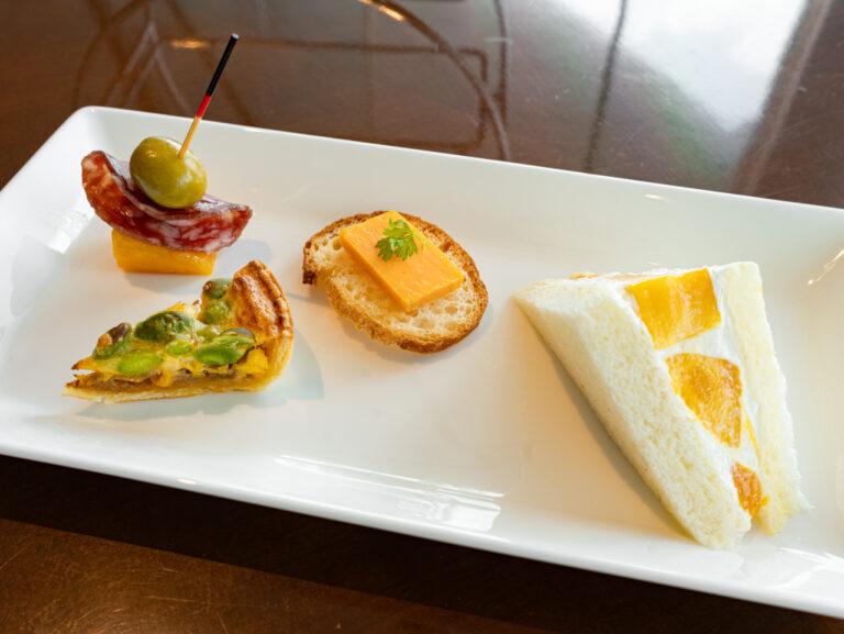 左から「マンゴーと生ハムのピンチョス」「とうもろこしと枝豆のキッシュ」「ウェールズ産チェダーチーズのブルスケッタ」「マンゴーのホイップサンドウィッチ」。