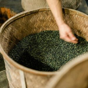 竹カゴに入れられた茶葉はゆっくりと炭火で燻される。均一に火が回るように手で混ぜる。