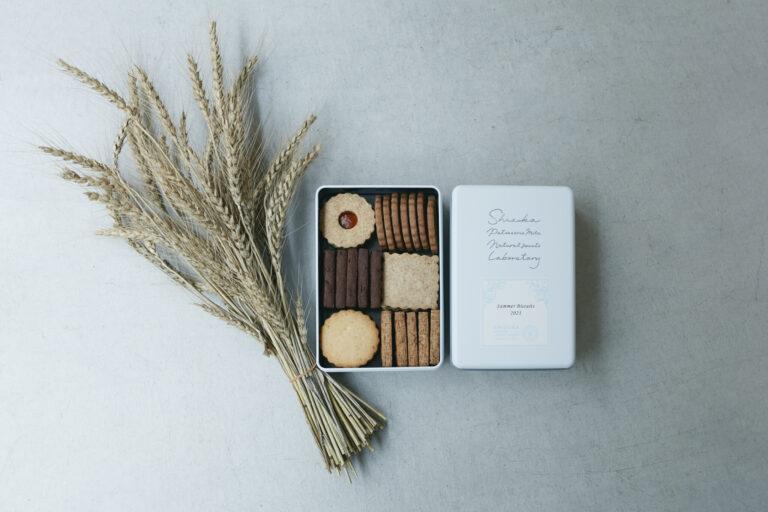 埼玉県産小麦を使用した看板のクッキー缶シリーズ。写真の夏限定缶はトロピカルフルーツジャムを挟んだサンドビスケット入り。5,983円。今夏収穫した新小麦の穂とともに。