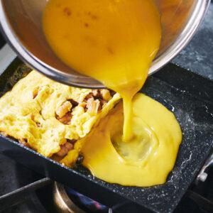 【POINT】半量の卵液を流し入れる。