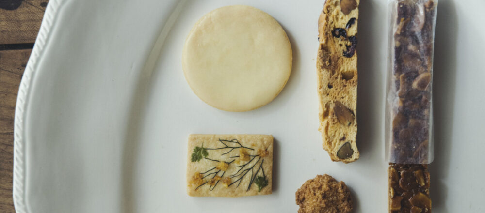 〈HORNO〉の焼菓子。左上から時計回りに、レモンクッキー(2枚入り)240円、ビスコッティ(3本入り)280円、フロランタン(2個入り)320円、プレーンスコーン300円、さつま芋とメープルシロップのマフィン370円、花のクッキー(3枚入り)340円、ココナッツクッキー(45g)280円
