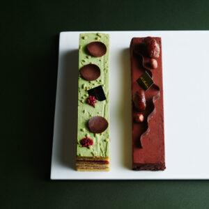 グリオットチェリー入りピスタチオケーキ、ビスキュイ・ショコラと自家製マロングラッセを合わせたチョコレートムースの2種類がセット。〈ドゥブルベ・ボレロ〉の「アンプレール・ショコラマロン&グリオット・ピスターシュ」2本入 5,400円(Webのみ)