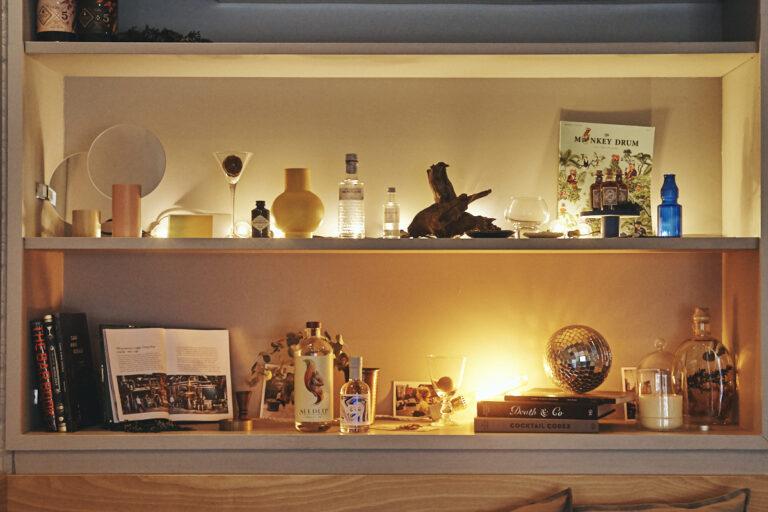 テーブル席の奥には、カクテルブックやバーにまつわるアイテムが並ぶ。