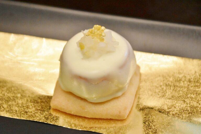 ショーフロワ仕立てにしたスモークサーモンを、ヘーゼルナッツのサブレにのせた「スモークサーモンロール」。柚子大根ととびっこがアクセントに。