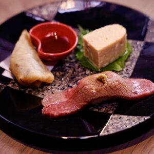 (写真手前から時計回りに)「サーロインの炙り寿司」「近江うし入り春巻き」「近江うしのだしを使った焼肉屋のだし巻」。