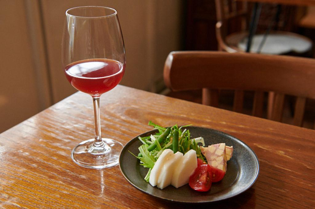 長野県・朝日村産のコンコード種ワインと、「本日の野菜盛り合わせ」400円~。野菜は近くの直売所〈こぐれ村〉で購入したもの。