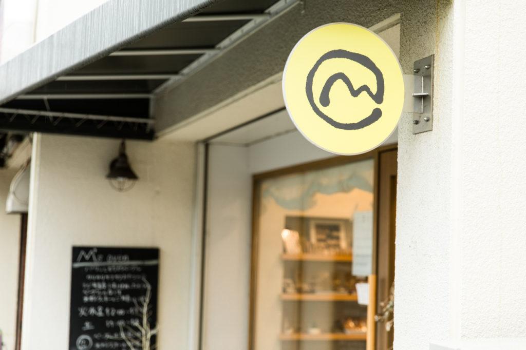 「西武柳沢」駅の南口を出て線路沿いの道へ。踏切の脇の黄色い「M」の看板がお店の目印。