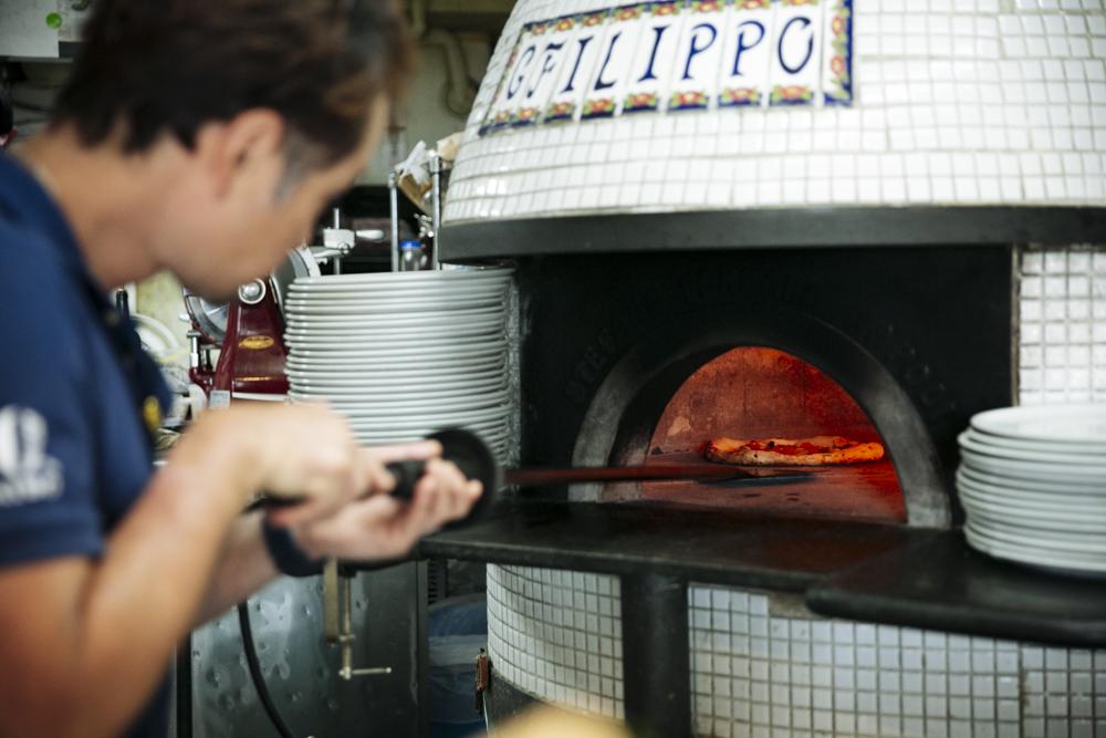 薪釜に入れて約1分半。長年培った職人の体感で焼き上げていく。平日は約100枚、休日は約200枚近くのピッツァを焼くそう。