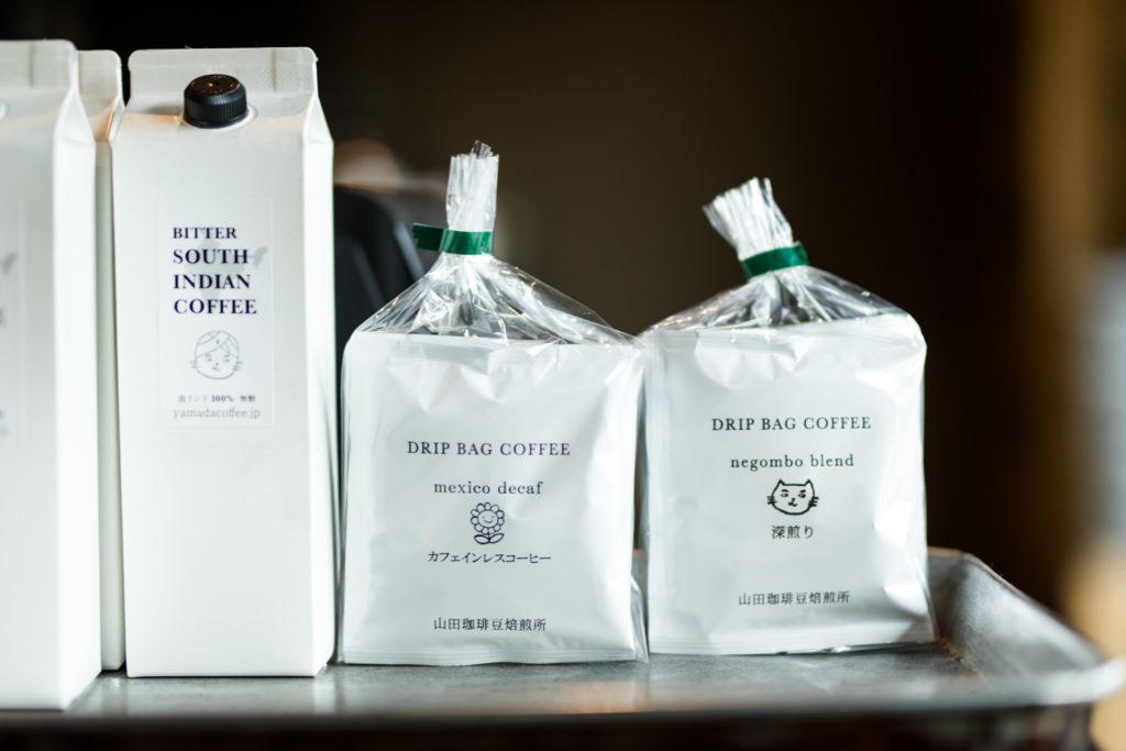 〈negombo 33〉の隣で奥さまが運営する〈山田珈琲豆焙煎所〉の商品も販売。カレーとコーヒーという最高のマッチングの提案を、夫婦の協働で実現しています。