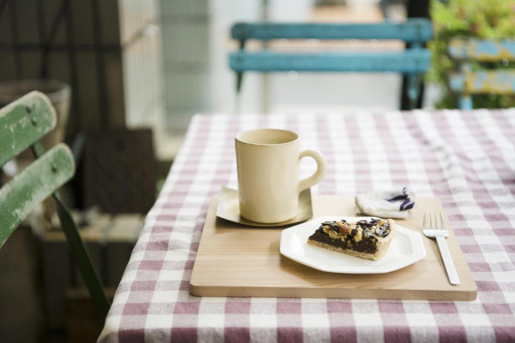 お店の外には小さなテラス席も。上石神井にある〈マンモスコーヒー〉の自家焙煎豆で淹れるコーヒー350円や、自家製の木の実のタルト300円で一服。