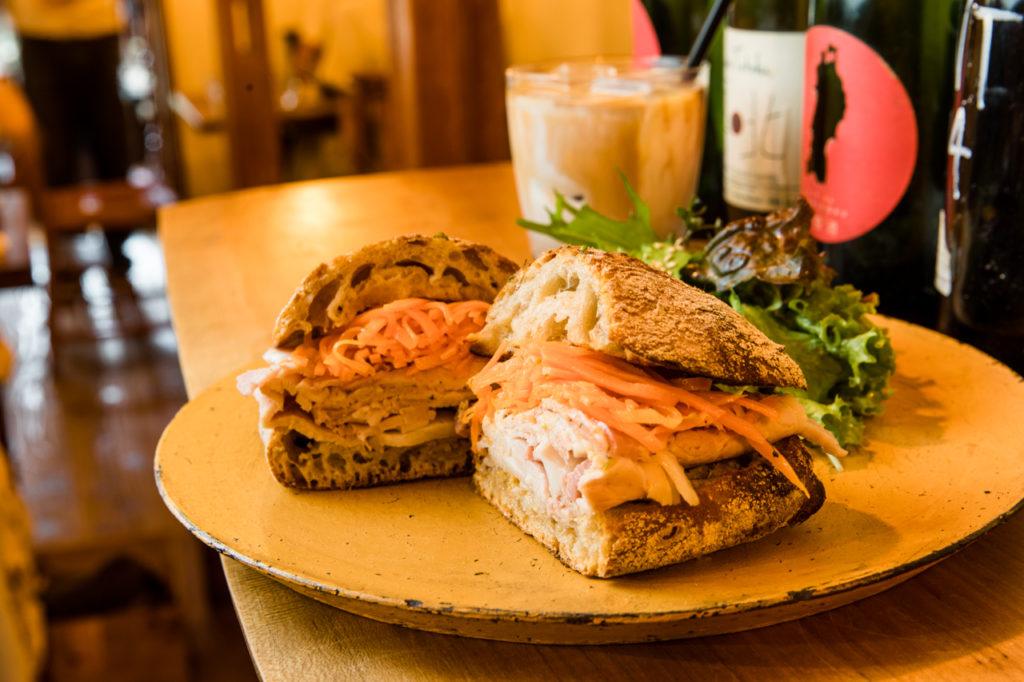お昼過ぎには売り切れも続出する大人気のサンドイッチ。パンは11種類の中から選べます。写真は「自家製ハムのサンド」ソフトドリンクセット1,140円。