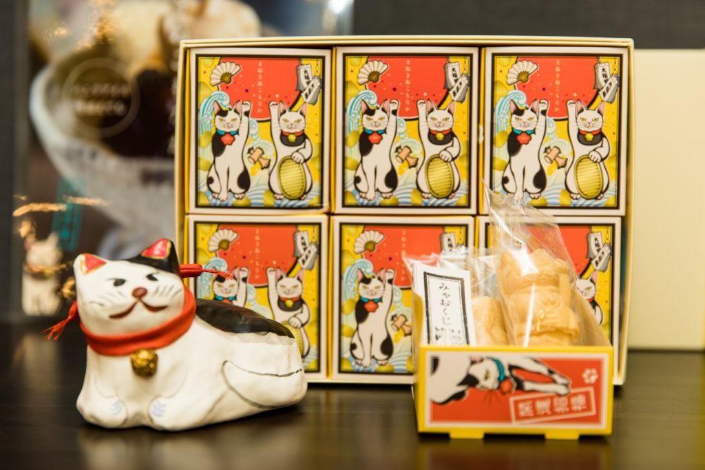 """みゃおくじ付き""""まねきねこもなか""""(2猫入り500円)もギフトにぴったりな人気者。別添えされている餡を食べる直前に挟めば、サクサクの最中が楽しめます。"""