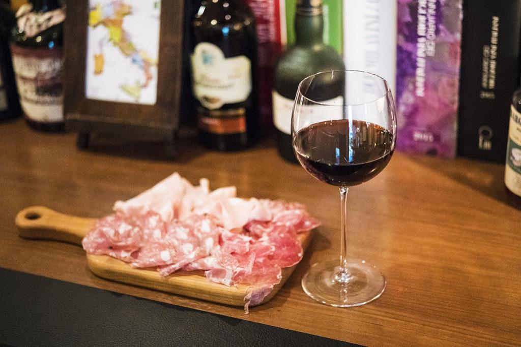 バーのフードはハムやチーズなど簡単なワインのアテを用意。生ハムやサラミが3種類味わえる「ハム盛り合わせ」700円、グラスワインは700円~。