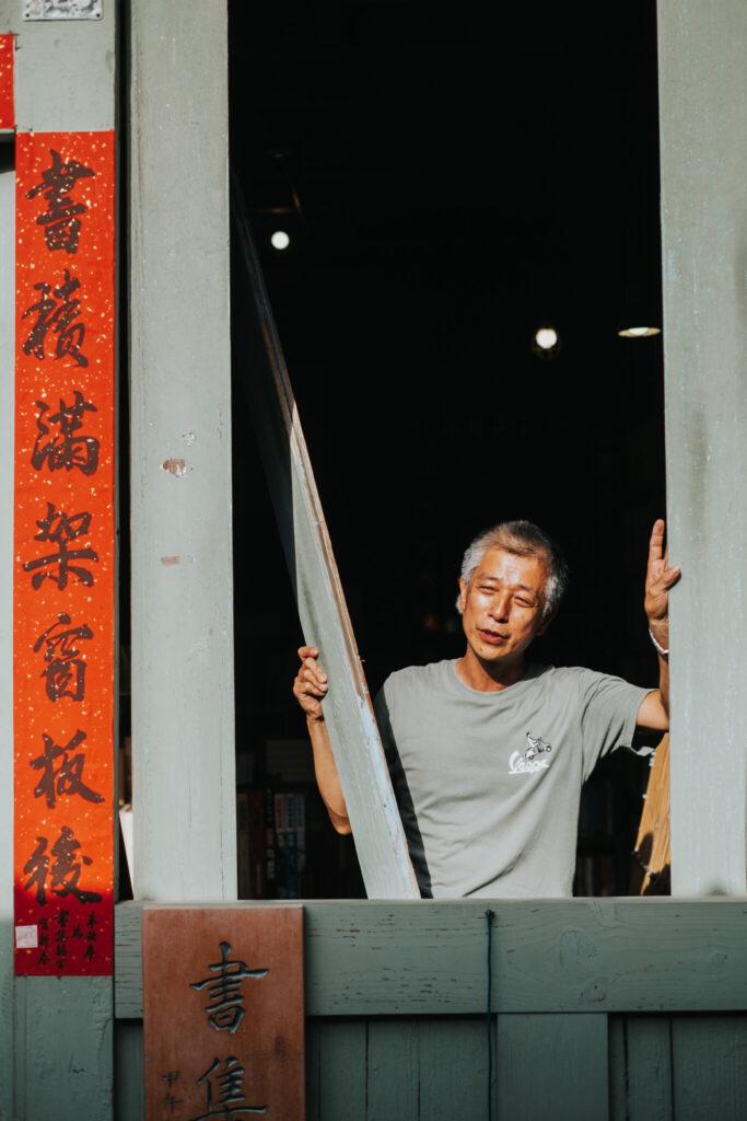 書集喜室的黃大哥正在拆卸窗板門.jpg 的副本